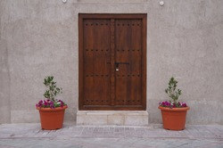 a vintage brown door with two pots