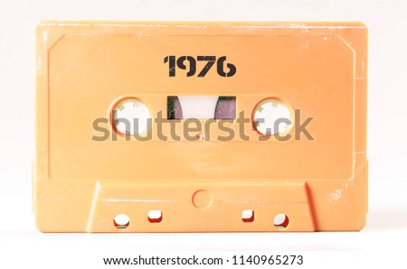 A vintage cassette tape from the 1980s era (obsolete music technology) with the text 1976 printed over it (my addition, not in the original image). Color: cream, sand. White background.