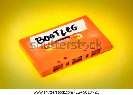 A vintage cassette tape (obsolete music technology), orange on a yellow surface, angled shot, carrying a label with the handwritten text Bootleg.