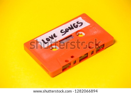 A vintage cassette tape (obsolete music technology), orange on a yellow surface, angled shot, carrying a label with the handwritten text Love Songs.  #1282066894