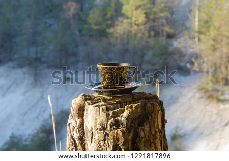 A vintage cup of aromatic coffee with milk stands on a stump in the mountains near the lake during a halt.