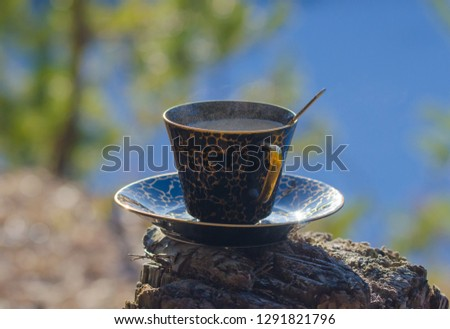 A vintage cup of aromatic, steaming  coffee with milk stands on a stump in the mountains near the lake during a halt.