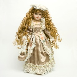 a vintage doll with a beautiful dress and golden tresses on the white background