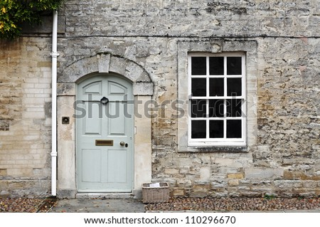 A vintage door and window on the facade of an old English cottage stone wall.