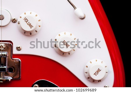 A vintage electric guitar's volume and tone controls.