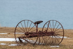 A vintage farm horse drawn hay rake in a field by an ocean.  There's hay on the ground with snow in places. The rake has its seat but is rusty. The ocean is blue in the background.