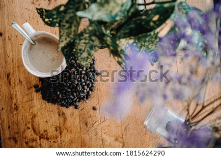 A vintage flat lay of a cup of coffee with grains of coffee near it and a plant decorating over a wood table Photo stock ©