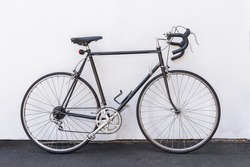 A vintage French road bike leaning against the white wall background.