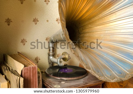 a vintage gramophone with a huge bell, dust and old records #1305979960