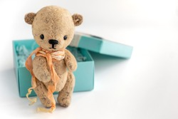 A vintage handmade teddy bear stands next to a gift box on a white background. Gift for an important holiday. Selective focus. Close-up. Copy space.