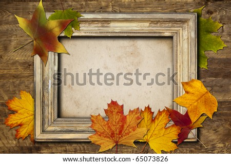 A vintage light frame and colored leaves on a wooden background