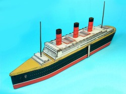 A vintage litho printed Crawford's biscuit tin toy ocean liner the Berengaria on a plain blue background.