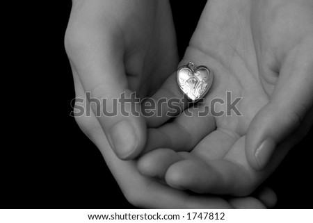 A vintage locket of a heart is held cradled in the palms of a woman's hands, as if she is tentatively offering her heart to someone.  Image is in black and white.