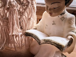 A vintage mid century Chinese figurine of a little boy in traditional costume reading a book positioned next to a macrame jar