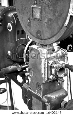 A vintage movie projector from an abandoned movie theater photographed in black and white.