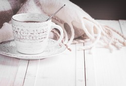 a vintage mug with hot coffee and spices decorated with a blanket in cage on a white wooden surface haze filter