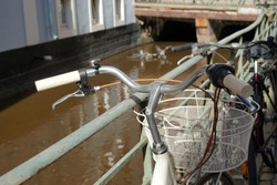 A vintage old bicycle leaned on a metal railing along a city stream in Freiburg in Germany called Baechle. It the stream on the background there is a skeleton of an old damage bicycle out of service.