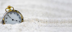 A vintage old black and gold watch in the sand in daylight.