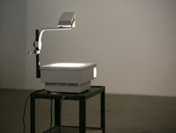 A vintage overhead projector sit on a roller cart lighting a wall ready to show overhead projection transparencies. Overhead projectors were often used in school & business before digital projection.