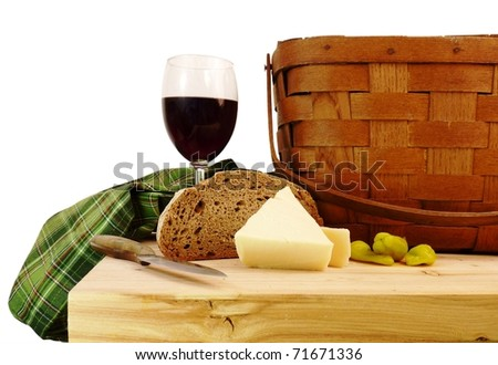 a vintage picnic basket on a rustic pine table with bread, cheese, and wine with a pure white background - stock photo