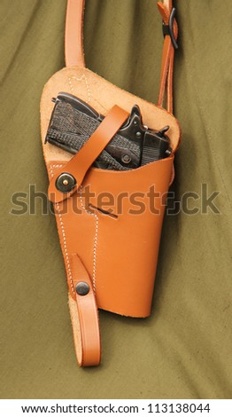 A Vintage Pistol Hand Gun Hanging in a Leather Holster.