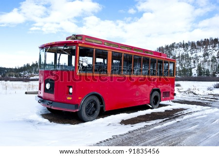A vintage red bus used today to transport tourists during sightseeing tours.
