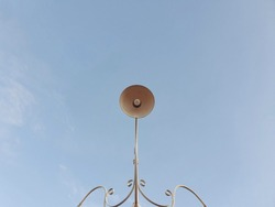 A vintage retro style street lamp made of painted white iron, beautifully decorated in a park against a blue sky background.