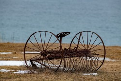 A vintage rusty hay rake sitting in a meadow with yellow grass and patches of snow. The farm rake has a round rusty seat and is a horse drawn farm tool. There's ocean in the background.