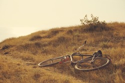 A vintage soviet iron bicycle lies on a yellow sun dried grass on the background of a sea surface in perspective and a bright scorching sun. Nostalgia from home, childhood.