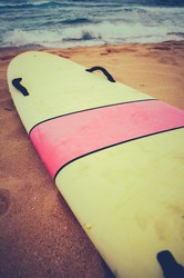 A Vintage Surf Board On A Deserted Wild Beach In Hawaii