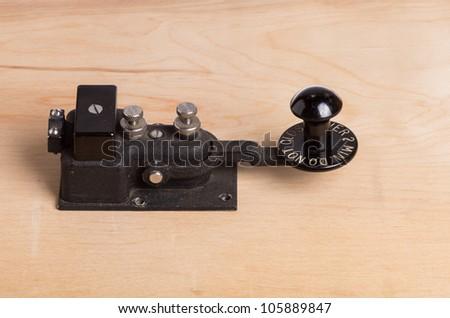 A vintage telegraph key sitting on a desk