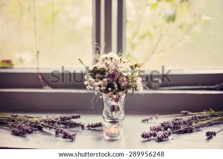 A vintage vase full of wild flowers in lilacs and creams. Vase is sat on window sill and surrounded by lavender. Vintage colour/color overlay added.