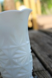 A Vintage white milk glass vase with a starburst pattern and fluted mouth used at an outdoor rustic table setting.