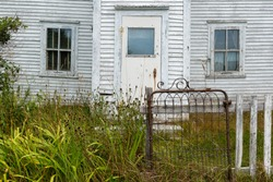 A vintage white wooden clapboard house with two windows and an old door. The garden in front of the house has grass and weeds growing up. An old wire gate is latched with a wood fence on one side.