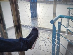 A violent male, boy, man, vandal,angry person breaks and destroys a window with a punch