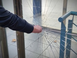 A violent, vandal,angry person breaks and destroys a window with a punch