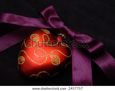 A violet satin ribbon tied in a bow over red hearts a pure black background.