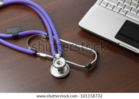 A violet stethoscope on a white laptop computer
