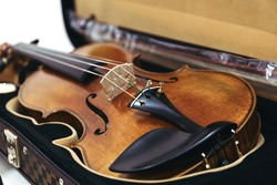 A violin in a dark open case. Classic stringed musical instrument. Selective focus. Close up.