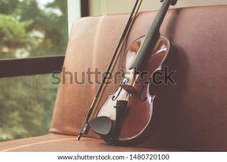 A violin leaning on a couch. #1480720100