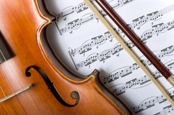 A violin or fiddle and bow on sheet music background