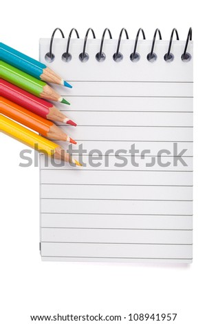 A vivid image with various colored pencils such as yellow, orange, red and blue on a notebook.