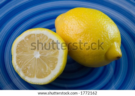 A vivid picture of  a sliced bright yellow lemon resting against a whole lemon.  Both lemons are sitting on a deep blue plate with a swirled pattern of different hues of blue.