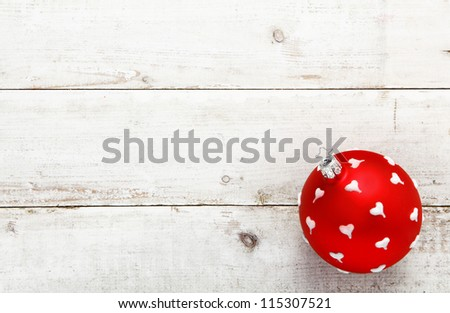A vivid red bauble dotted with white hearts suitable as a Christmas or Valentines decoration on a background of white wooden boards with copyspace