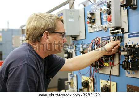 A vocational education teacher wiring a motor control board.  All work depicted is accurate and being performed according to national code and safety regulations.