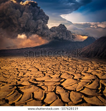 A volcano looks over a cracked earth landscape