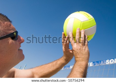 A volleyball player lobs a ball during a game at the beach.
