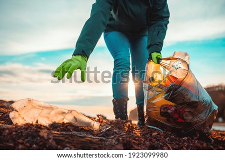A volunteer collects garbage on a muddy beach. Close-up. The concept of Earth Day. Bottom view. Сток-фото ©