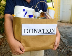 A volunteer delivers a donation bag filled with food and cleaning supplies during the Covid-19 / Coronavirus Pandemic