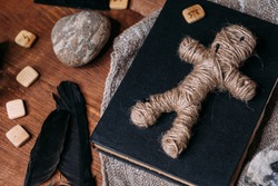 A voodoo doll made of rope lies on a black book, surrounded by magical ritual objects: candles, stones, crow feathers. Halloween concept